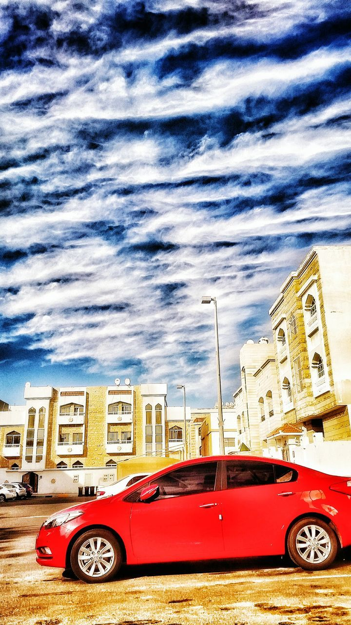 car, land vehicle, transportation, architecture, building exterior, mode of transport, red, built structure, stationary, no people, sky, city, outdoors, day