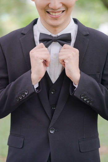 Midsection of businessman wearing tuxedo while standing outdoors