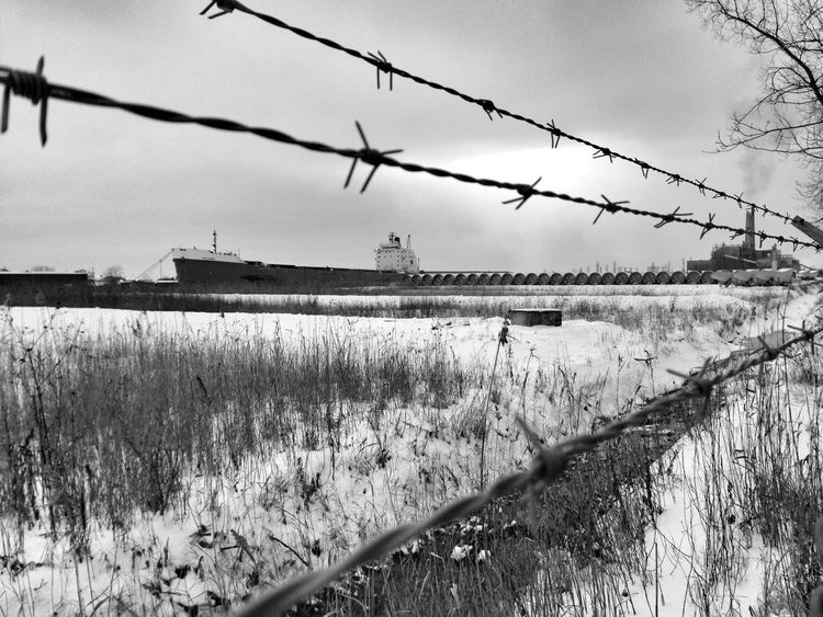 Freighter on Detroit River Behind Barbed Wire Protection Fence Water Sky Barbed Wire Tranquility Nature Scenics Growth Tranquil Scene Day Outdoors Growing No People In Front Of Cloud - Sky Remote Beauty In Nature Non-urban Scene Detroit Windsor Ontario Detroit River Dramatic Angles