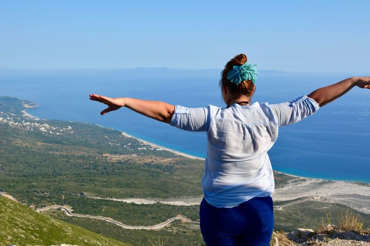 Rear view of woman standing with arms outstretched looking at sea