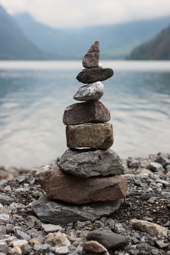 Stack of stones in sea against sky on sunny day