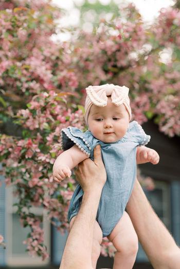 Full length of cute baby girl against pink flowering plants