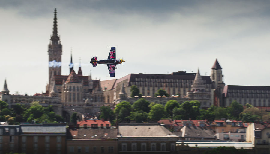 aerobatic plane flying in front of the fishermans bastion in budapest Sky Building City Travel Destinations Nature Tower Travel Tourism History Spirituality Day Belief The Past No People Outdoors Spire  Airplane Acrobatic Activity RedBull Flying Fast Aerobativ Piloting