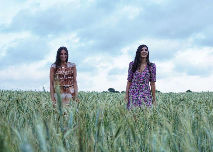 Women standing on field against sky