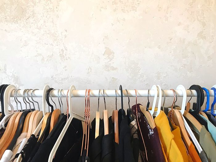 Row of clothes hanging on rack against wall