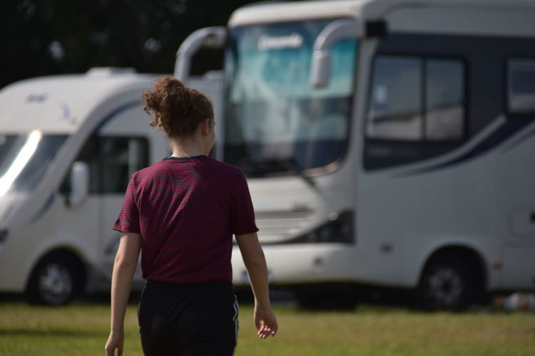 Rear view of woman standing in front of motorhomes
