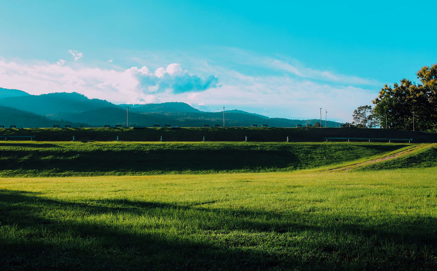 The view of the mountains, meadow and sky as the backdrop. Beauty In Nature Cloud - Sky Environment Field Grass Green Color Land Landscape Meadow Mountain Nature No People Outdoors Plant Sky Tranquil Scene Tranquility Tree