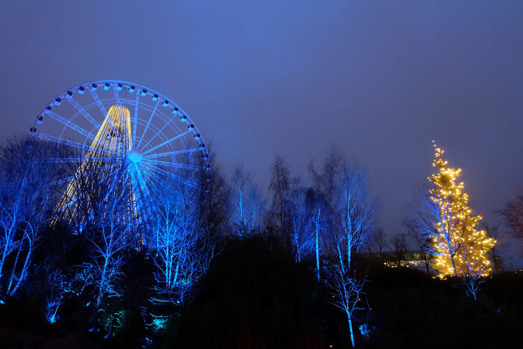 Low angle view of illuminated ferris wheel and bare trees against clear sky at dusk