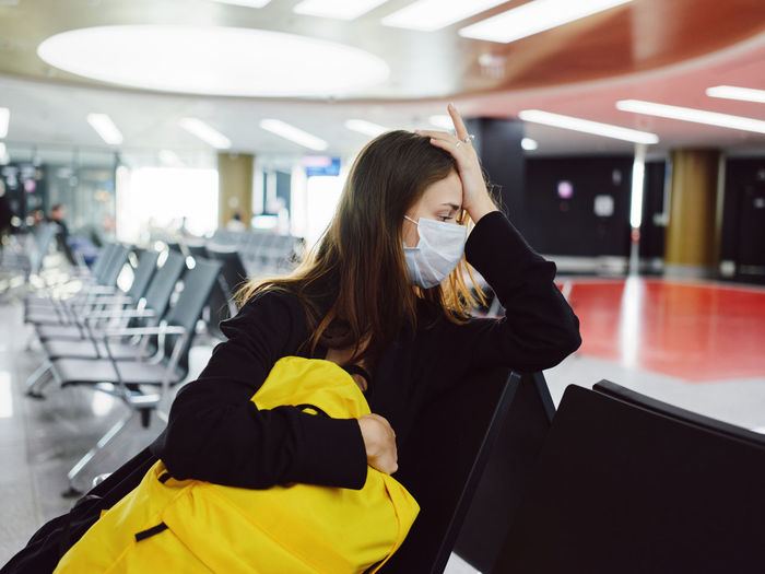 Young woman sitting on seat at airport