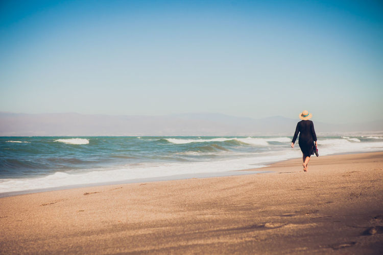 Rear View Of Woman Walking At Sea Shore Against Clear Sky