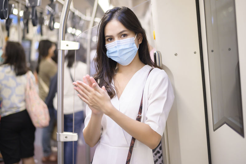 Portrait of woman wearing mask standing in subway train