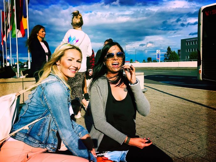 Happy friends sitting in city