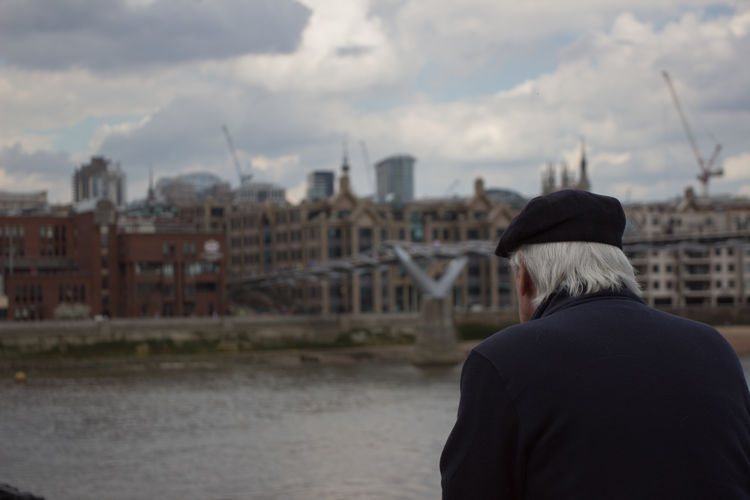 Rear view of senior man by thames river against sky