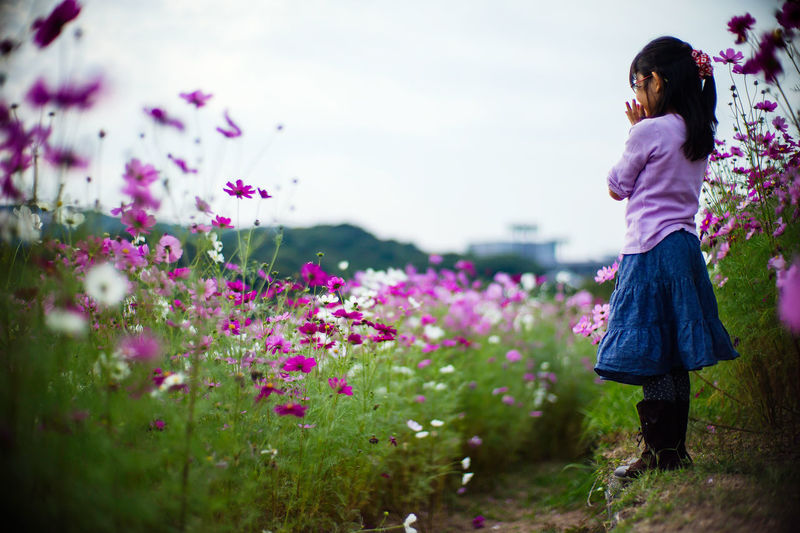 Girl Standing On Field By Plants Against Sky