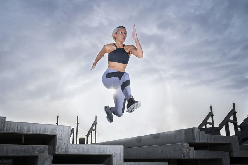 Middle Eastern Girl with short braided hair jumping of a stack of blocks on a construction site wearing gray and black fitness outfit on a hot bright sunny day. Exercising Jumping Off Rocks Sitting Architecture Arms Raised Bright Day Built Structure Cloud - Sky Day Dusty Effort Fitness Model Full Length Hot Day ☀ Jumping Lifestyles Low Angle View Mid-air Middle Eastern Woman Motion Nature One Person Outdoors Real People Sky Sport Sports Clothing Stretching Teenager Vitality Young Adult