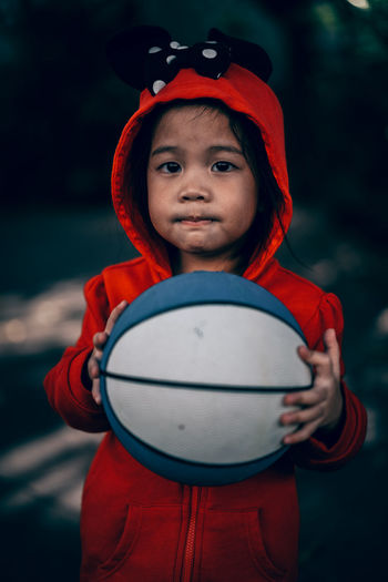Portrait of cute boy holding ball while standing outdoors