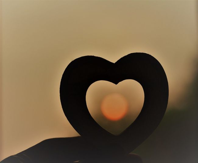 Close-up of silhouette heart shape against sky during sunset