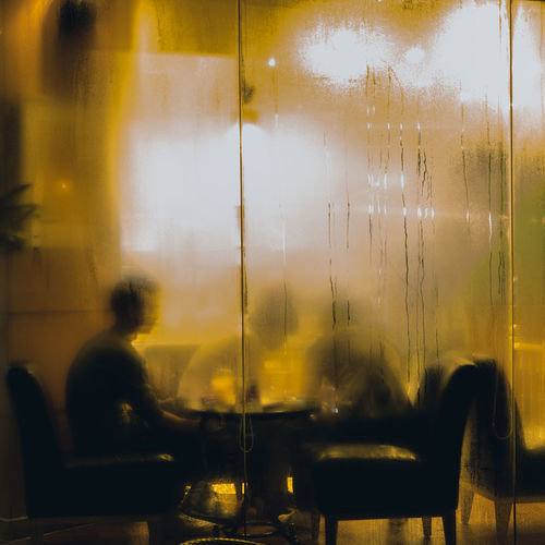 Blurred motion of people sitting in glass window