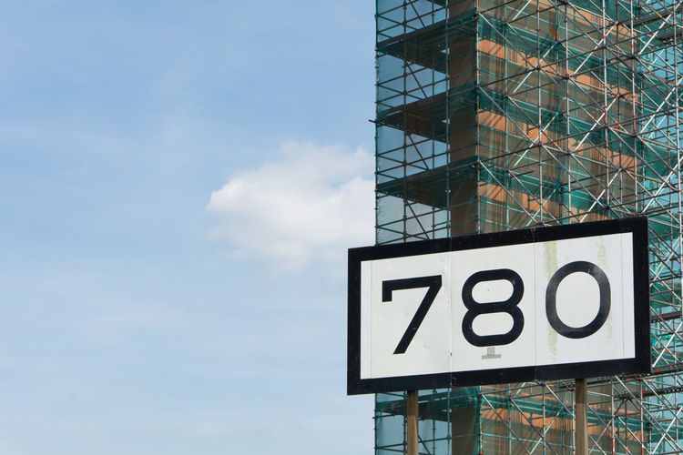 Low Angle View Of Number On Billboard Against Building