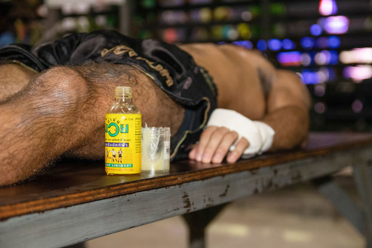 Midsection of man lying down on bottle
