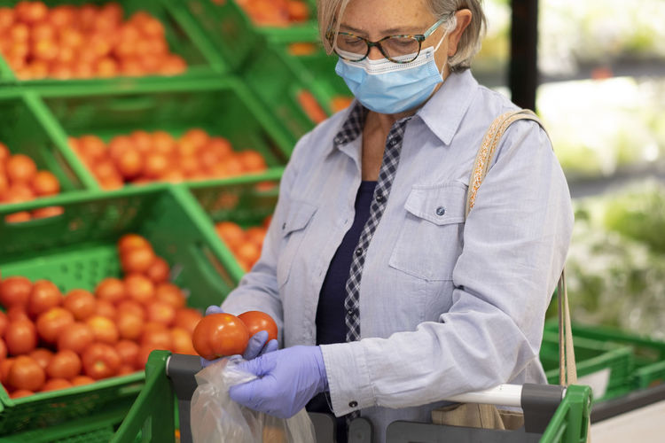 Senior woman wearing mask shopping at store