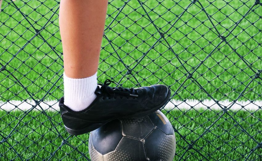 Low section of sportsperson with soccer ball standing by net on playing field