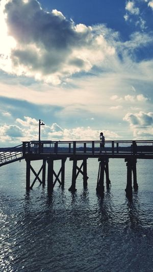 Silhouette teenage boy standing on pier over sea against cloudy sky
