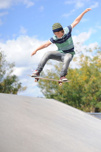 Boy skating mid air Skatepark Childhood Day Energetic Full Length Fun Happiness Jumping Leisure Activity Mid-air Motion Nature One Person Outdoors People Real People Skate Trick Skater Boy Skating Sky Tree The Street Photographer - 2018 EyeEm Awards 10 Summer Sports