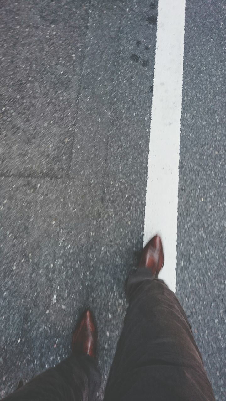 human leg, low section, road, personal perspective, road marking, asphalt, real people, one person, human body part, high angle view, street, outdoors, day, standing, walking, white line, shoe, transportation, men, close-up, people