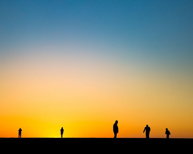 Silhouette People On Landscape Against Clear Sky During Sunset
