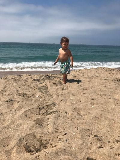 Full length of shirtless boy standing on sandy beach