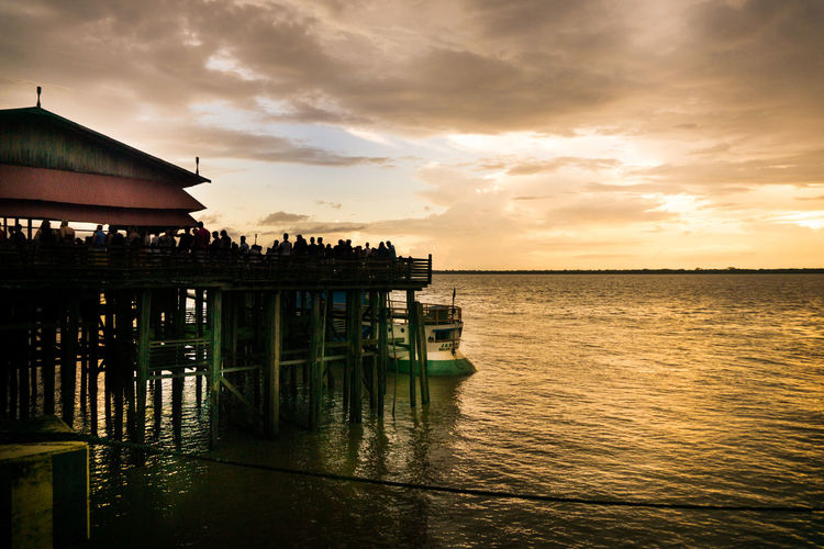 EyeEm Selects Sea Water Architecture Sunset Built Structure Beach Reflection Stilt House Travel Destinations Outdoors Waterfront Sky Travel Horizon Over Water Cloud - Sky Scenics Nature