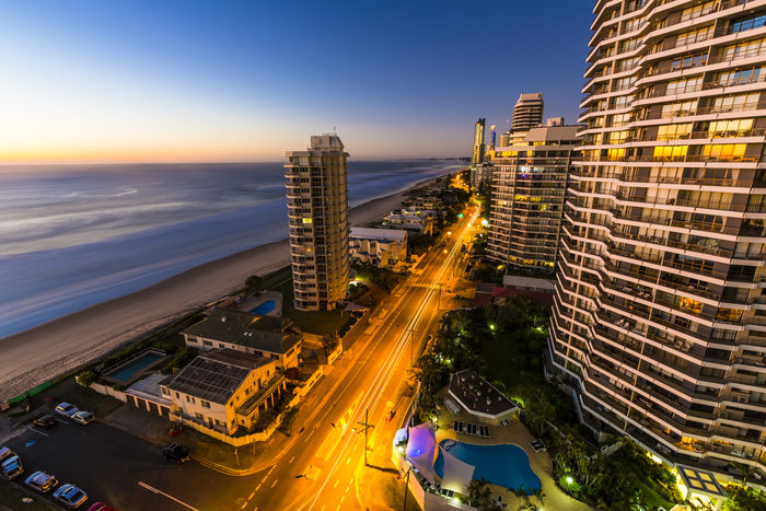Early morning, first light sunrise looking along a street-lit avenue on the Gold Coast, Australia. Gold Coast Night Lights Sunrise Silhouette Surfers Paradise Aerial View Architecture Beauty In Nature Building Exterior Built Structure City City Life Cityscape First Light Illuminated Modern No People Ocean Outdoors Road Sky Skyscraper Sunset Travel Destinations Urban Skyline Warm