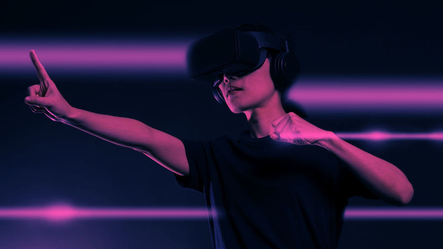 Woman wearing virtual reality simulator against abstract background