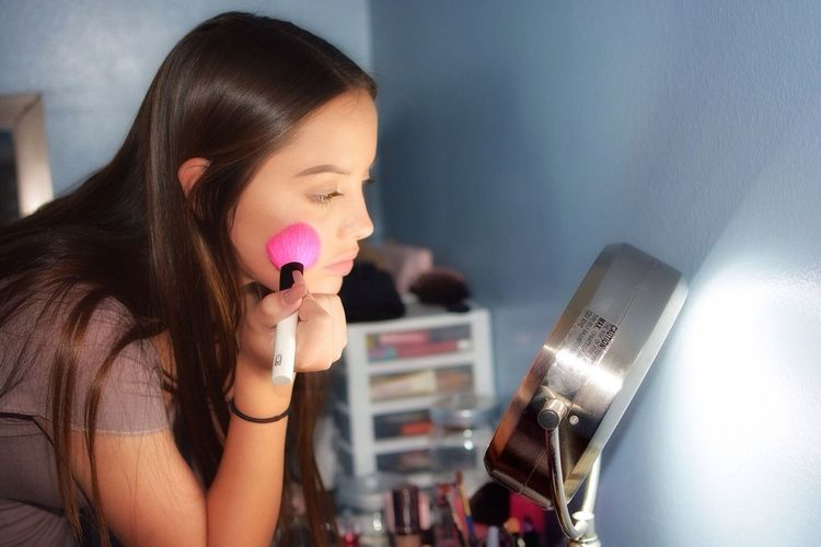 Young woman applying make-up at home