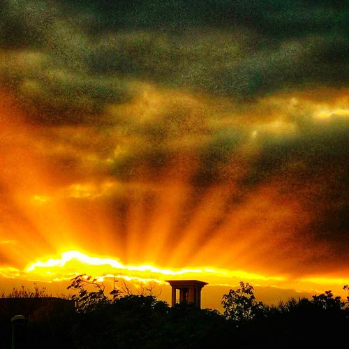 Amazing Sunbeams as the Sun sets through the clouds IPhoneography Cloud - Sky Dramatic Sky Sky Sunset Built Structure Beauty In Nature Nature Tranquility Scenics Orange Color