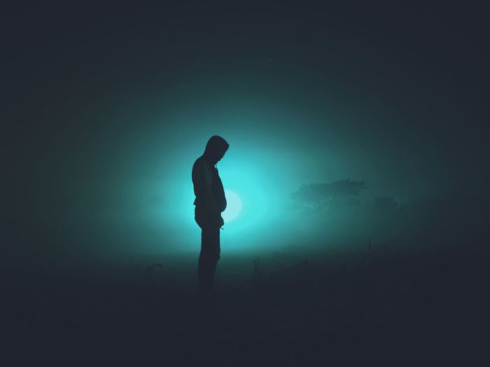 Side view of silhouette man against sky at night
