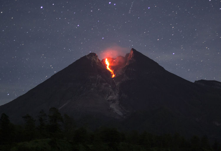 Low angle view of volcano against sky at night