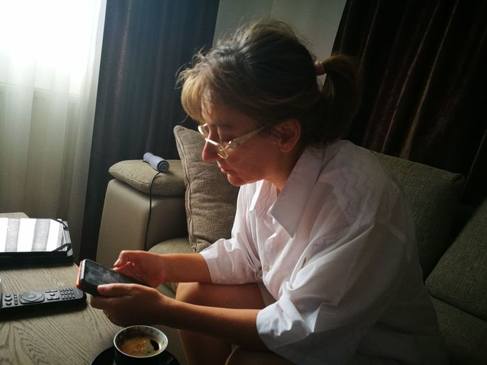 Woman Drinking Coffee Woman Reading Hair Dryer Morning Coffee Morning Technology EyeEm Selects Human Hand Living Room Wireless Technology Sitting Women Domestic Life Eyeglasses  Bedroom Curtain