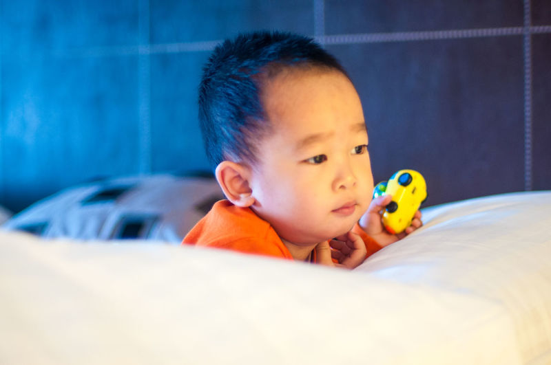Cute boy looking away while holding toy on bed at home