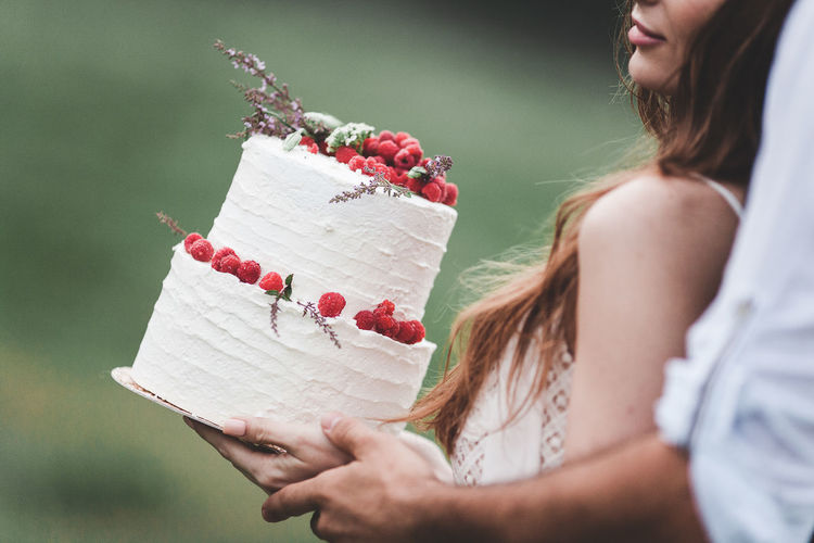 Midsection of couple holding wedding cake at farm