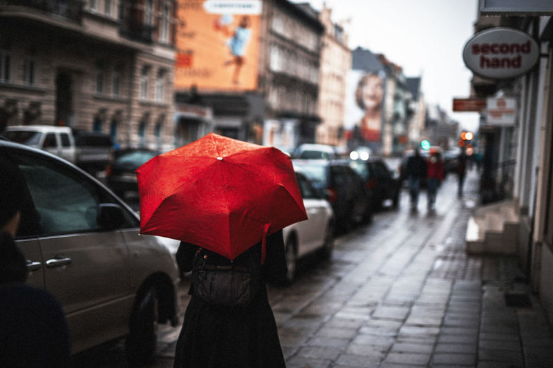 Rear View Of Woman Walking With Red Umbrella On Sidewalk In City During Rainy Season
