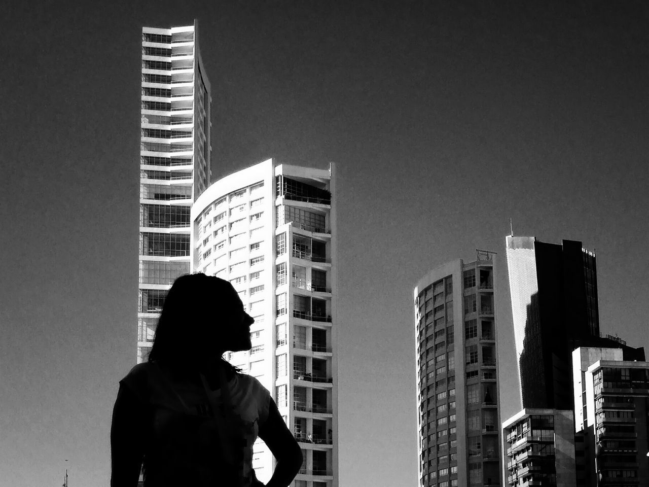 Woman standing against tall buildings against clear sky in city