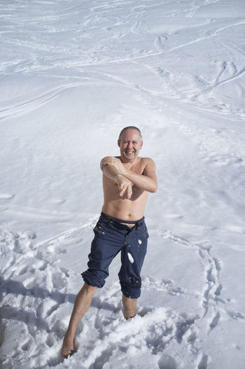 Portrait of shirtless man in snow