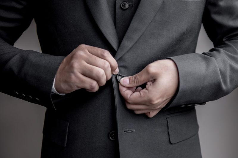 Midsection of businessman closing blazer button