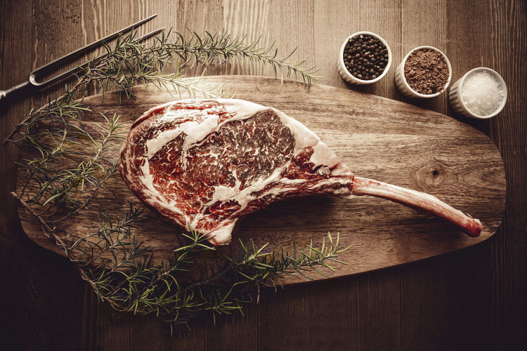 Raw dry aged wagyu tomahawk steak on a wooden background with salt, pepper, rosemary and a fork