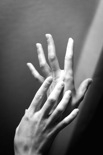 Close-up of hands against gray background