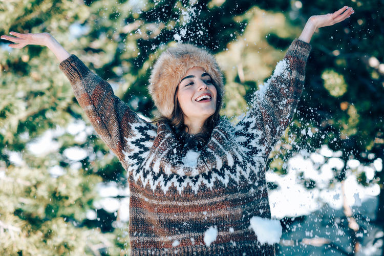 Woman with arms raised in snow