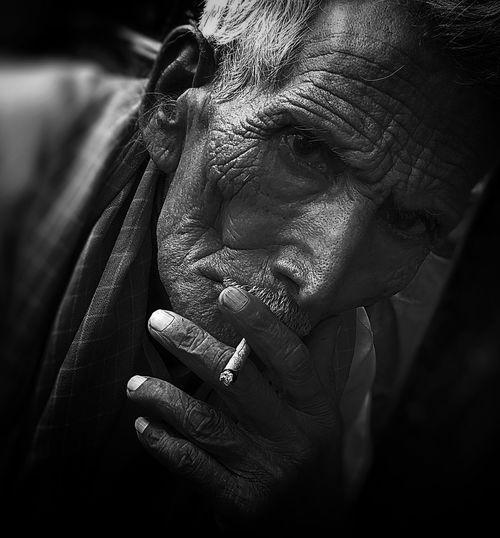 Close-up portrait of man smoking cigarette