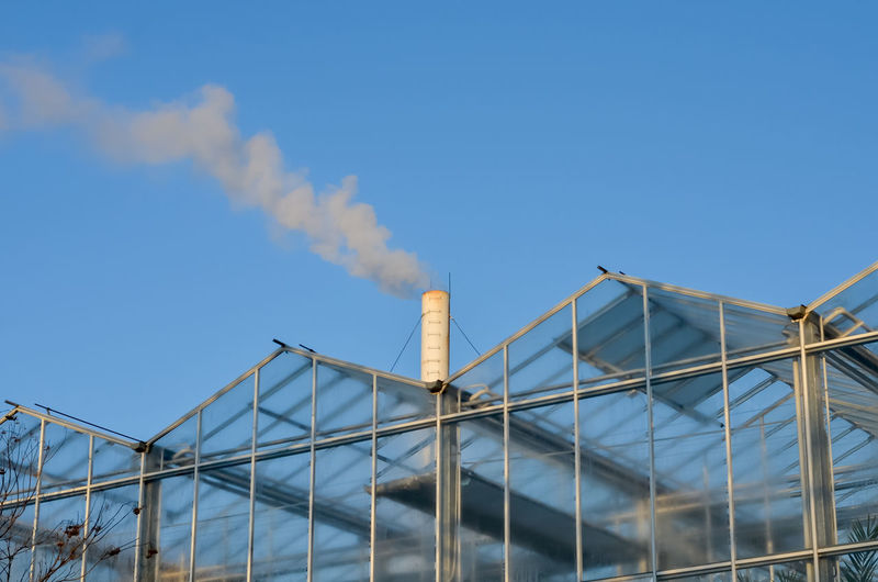 Glass greenhouse with smoking pipe emitting smoke against blue sky . Heating the greenhouses in winter .Environmental pollution. Cold Season Winter Greenhouse Windows Glass Heating Air Atmosphere Blue Chemical Chimney Cleanliness Climate Contaminate Contamination Damage Dioxide Dirty Ecology Emission Emit Emitting Energy Environment Environmental Factory Fuel Fumes Gas Global High Human Industrial Industry Ozone Pipe Pollute Polluting Pollution Power Sky Smog Smoke Smokestack Steam Technology Tower Toxic Vapor Warming